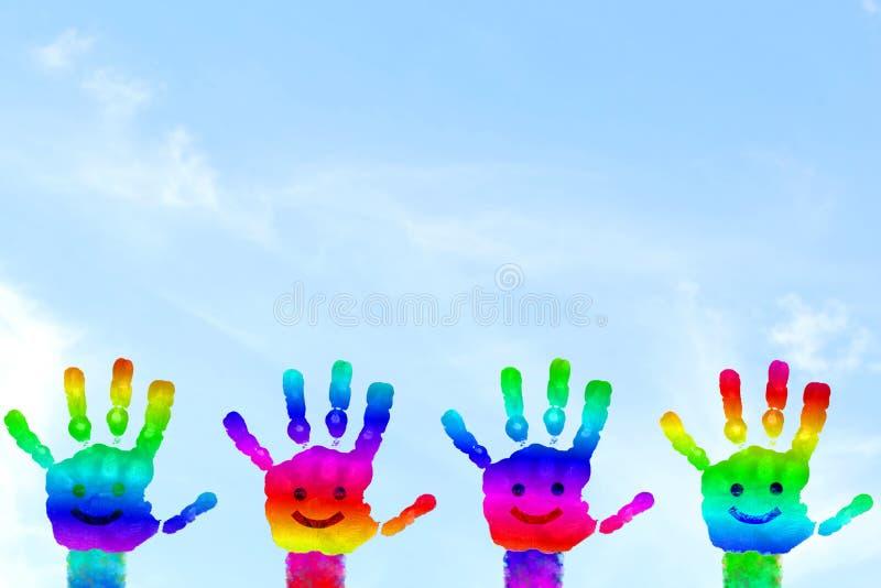 A mão colorida pintada crianças do arco-íris da arte da mão imprime no fundo do céu imagem de stock royalty free