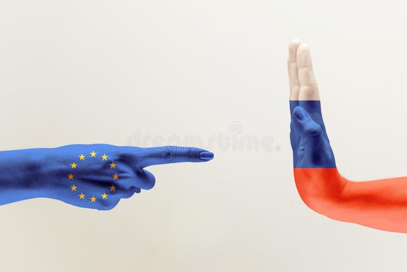A mão coloriu nas bandeiras da UE e da Rússia fotografia de stock
