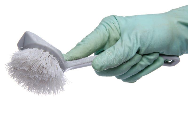 Mão com as luvas do prato que guardam uma escova fotografia de stock