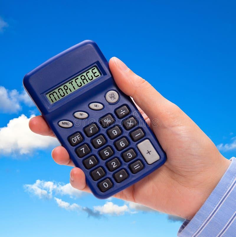 Mão com calculadora da hipoteca fotografia de stock royalty free