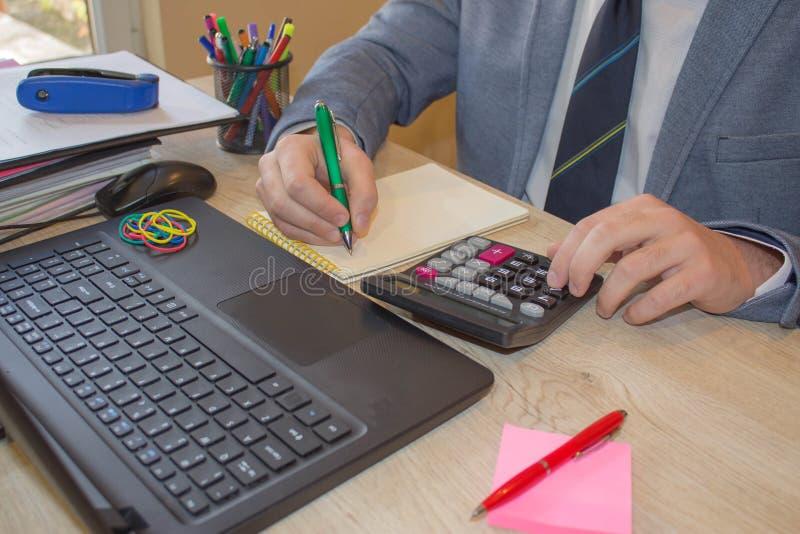 Mão com calculadora Negócio da finança e da contabilidade Homem de negócios novo Calculating Finance Bills no escritório fotos de stock royalty free