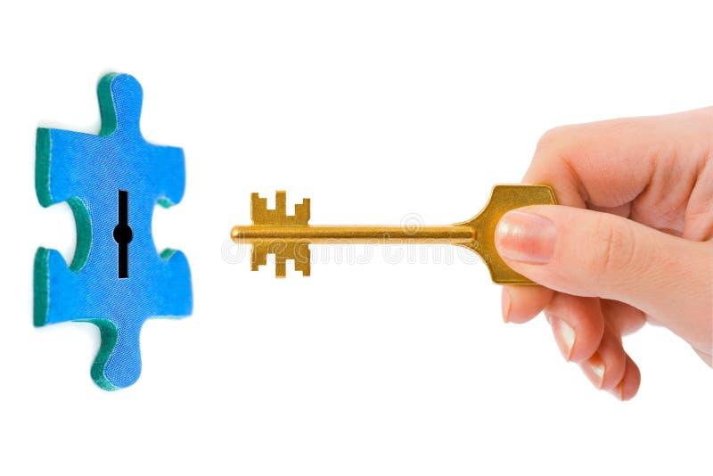 Mão com chave e enigma foto de stock