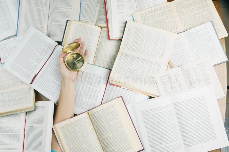 Mão com compasso entre muitos livros foto de stock royalty free