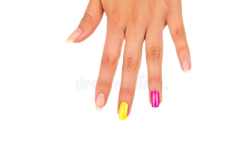 A mão com dedos espalhou para fora de cima dos pregos do close up visíveis em cores diferentes rosa, amarelo e natural, brancos imagem de stock royalty free
