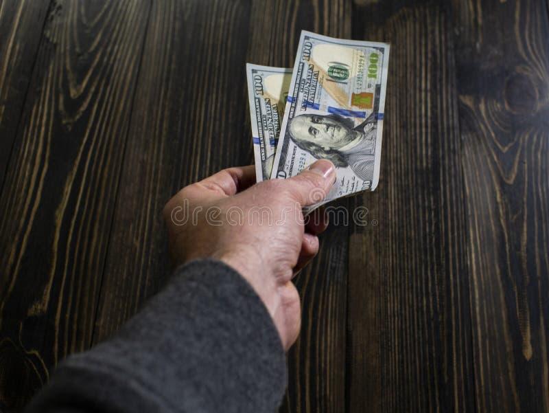 Mão com dinheiro em um fundo de madeira mão que guarda dois 100 dólares de cédula Dólares americanos na mão do homem fotografia de stock royalty free