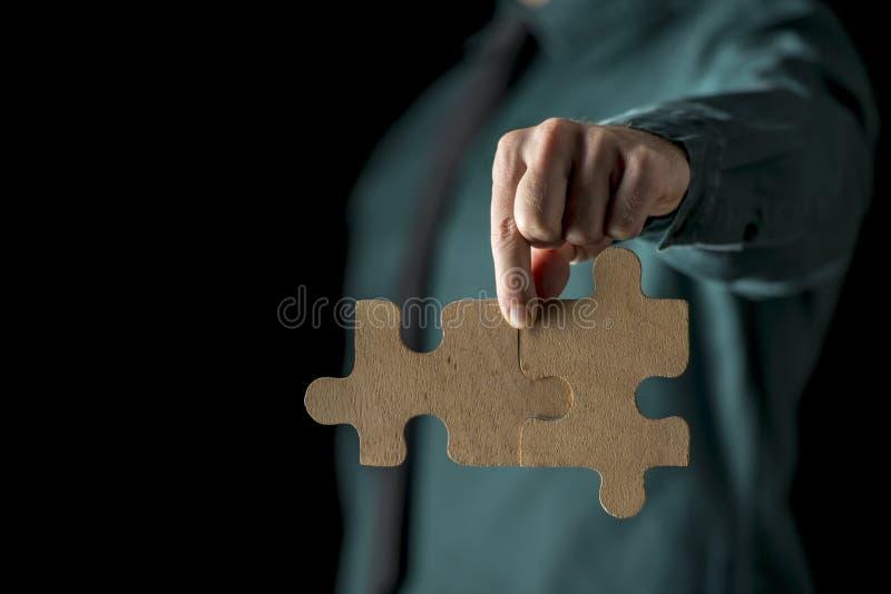 Mão com duas partes do enigma fotografia de stock