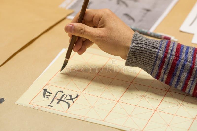 Mão com exercício da caligrafia da escova de pintura fotos de stock