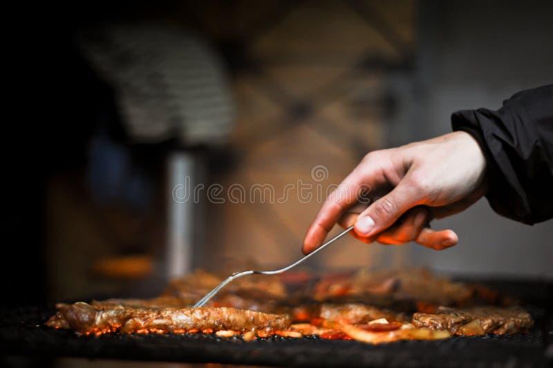 Mão com a forquilha que gira a carne grelhada deliciosa com o vegetal sobre os carvões em uma grade do BBQ foto de stock royalty free