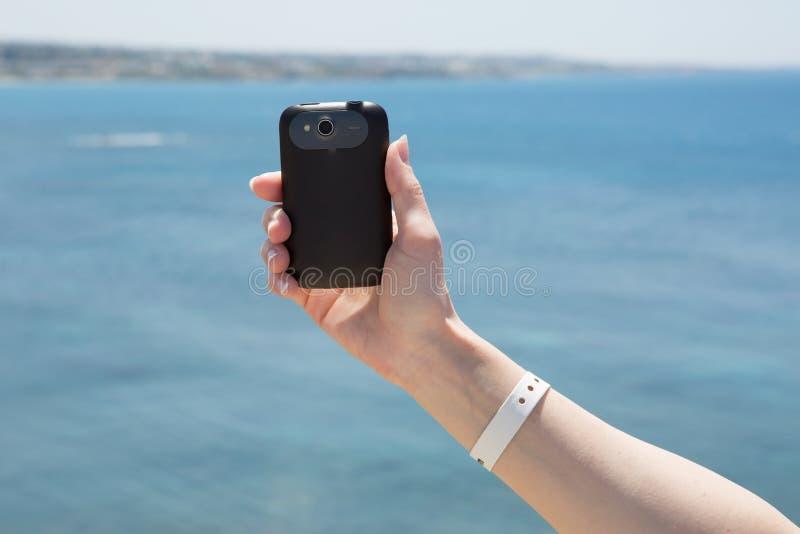 Mão com fotografia do auto do smartphone imagens de stock royalty free