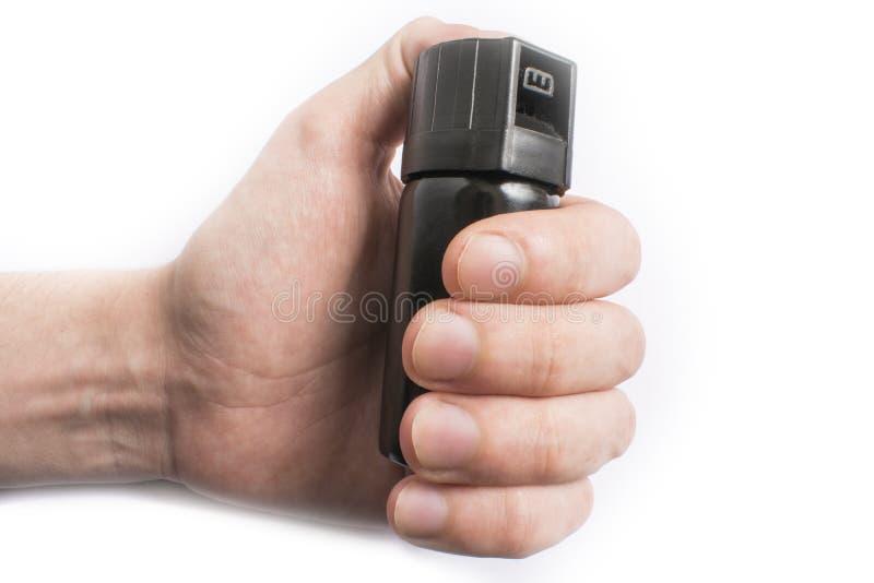 Mão com a garrafa do spray de pimenta isolada no fundo branco fotos de stock royalty free