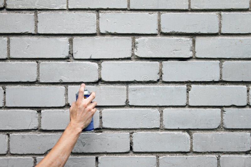 Mão com a lata de pulverizador dos grafittis na frente da parede de tijolo imagens de stock