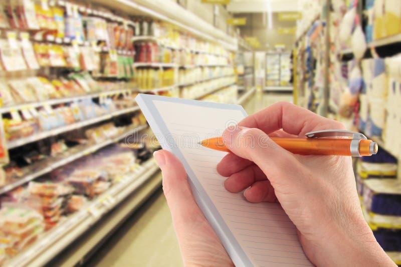 Mão com lista de compra da escrita da pena no supermercado