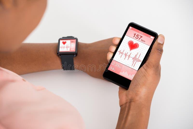 Mão com móbil e Smartwatch que mostra a taxa da pulsação do coração foto de stock royalty free
