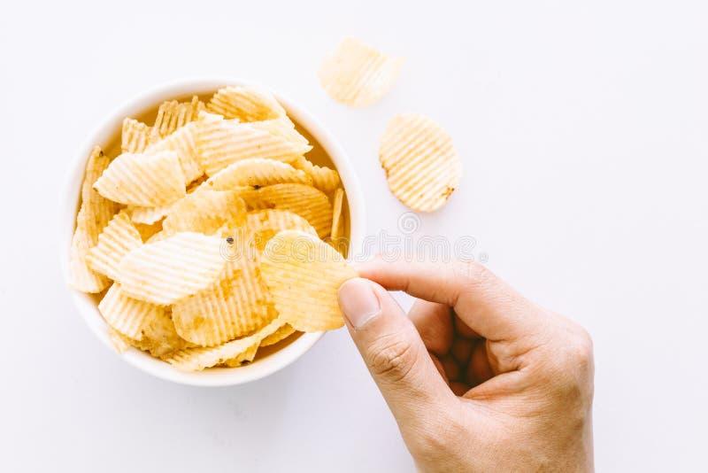 Mão com microplaquetas e bacia de batata no fundo branco fotos de stock royalty free