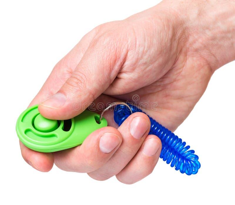 Mão com o clicker do cão no branco fotografia de stock