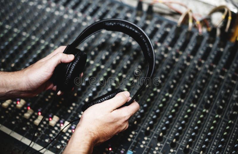 Mão com o fones de ouvido no misturador sadio imagem de stock royalty free