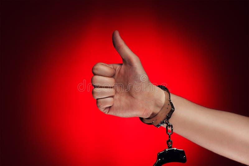A mão com o polegar ascendente e as algemas abriu o conceito imagens de stock royalty free