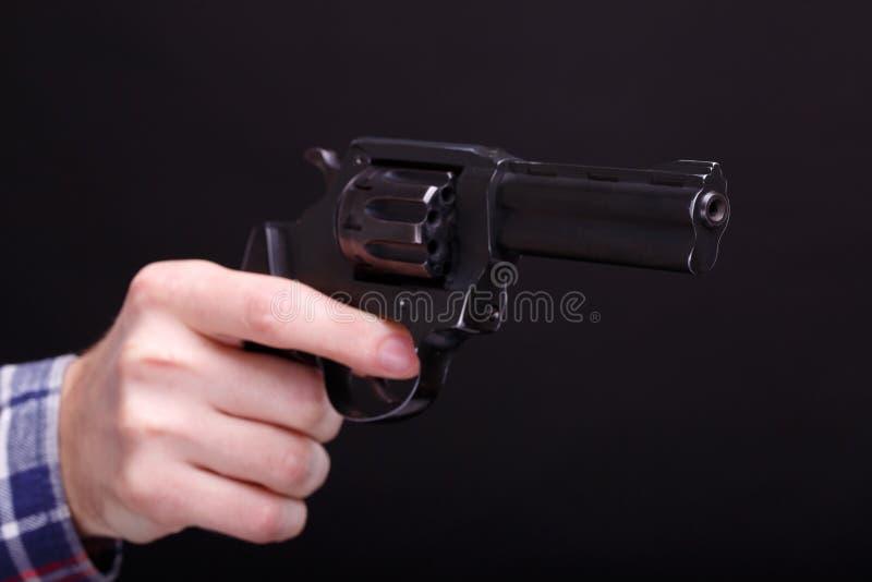 A mão com o revólver imagem de stock