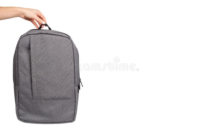 Mão com o saco de escola cinzento de matéria têxtil, trouxa da rua da cidade imagens de stock