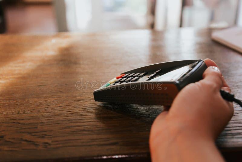 A mão com o terminal e o cartão de crédito do cliente Pagamento pelo cart?o fotografia de stock royalty free