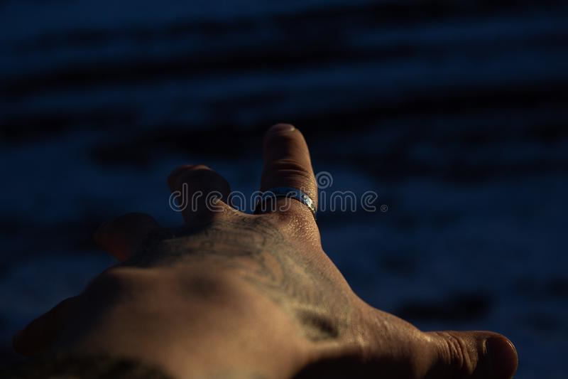 A mão com os alcances do anel para a água foto de stock