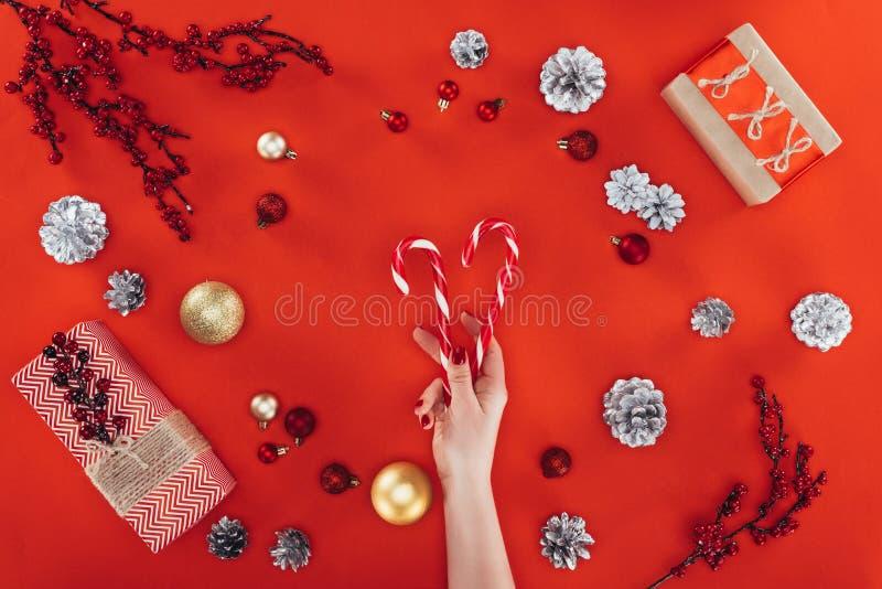 Mão com os bastões de doces no christmastime foto de stock royalty free