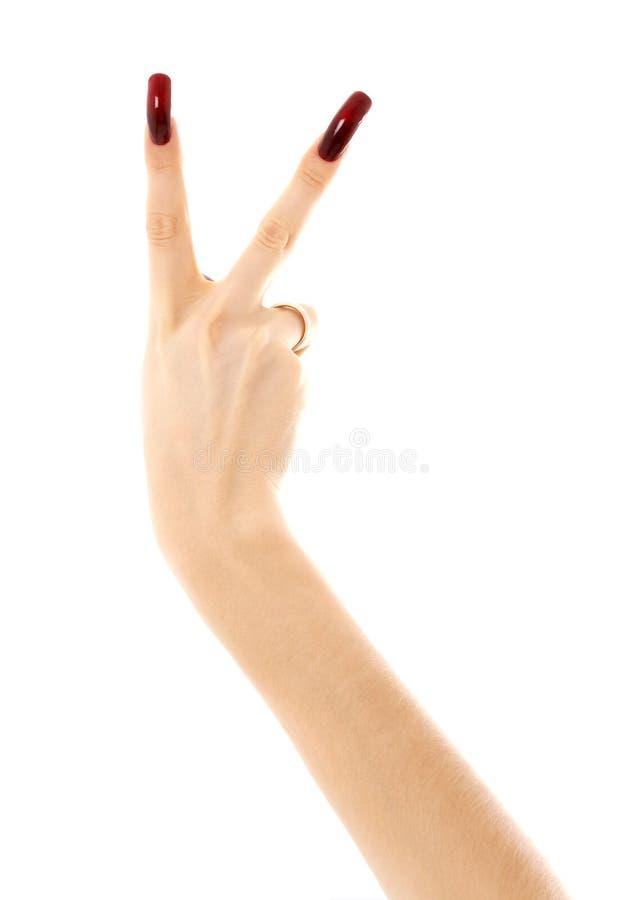 A mão com os pregos acrílicos longos que mostram a vitória assina fotografia de stock