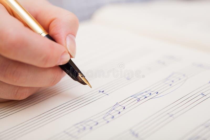Mão com pena e folha de música fotos de stock royalty free