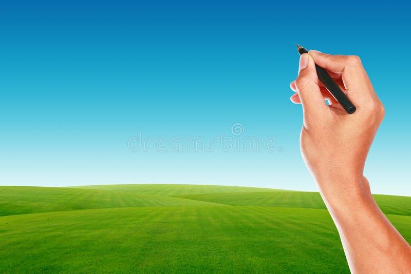 Mão com a pena no campo de céu azul e de grama verde imagem de stock royalty free