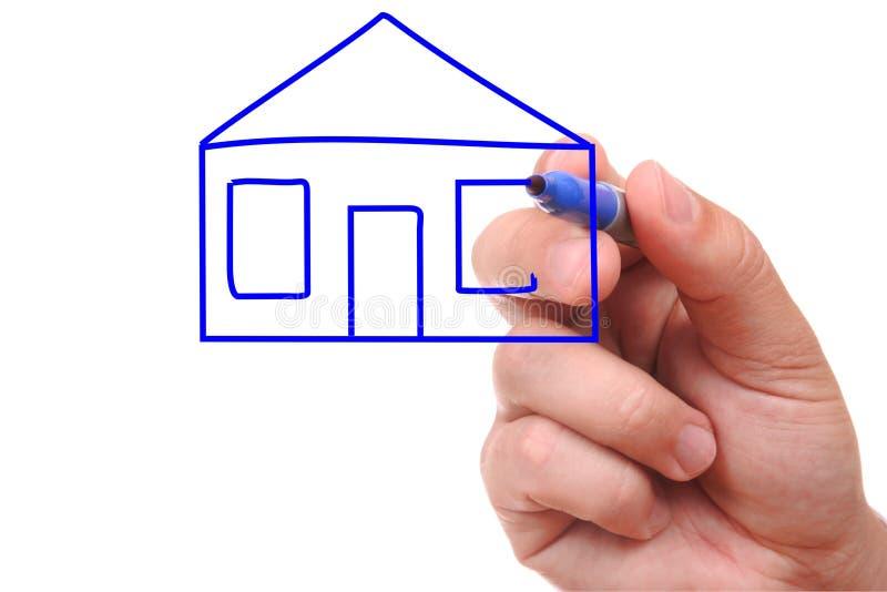 Mão com a pena que desenha uma casa imagens de stock