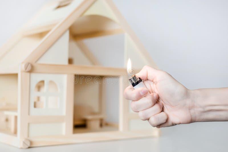 Mão com queimadura mais claro contra o modelo de madeira da casa no fundo Incêndio do conceito da casa Acidente criminoso fotos de stock royalty free