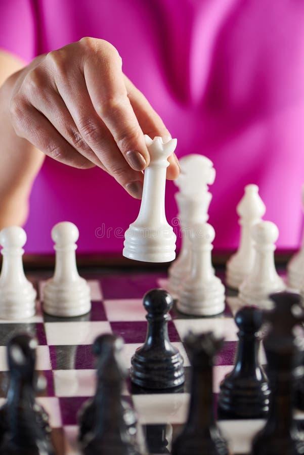 Mão com a rainha branca sobre o tabuleiro de xadrez imagens de stock royalty free
