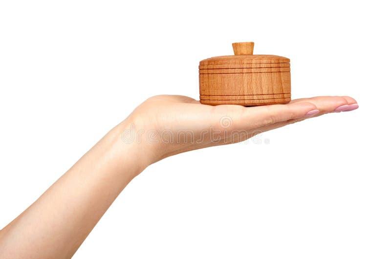 Mão com recipiente de madeira, caso redondo Fundo isolado ilustração stock
