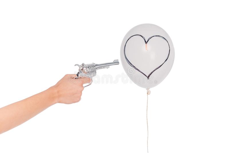 Mão com revólver e balão com coração imagens de stock