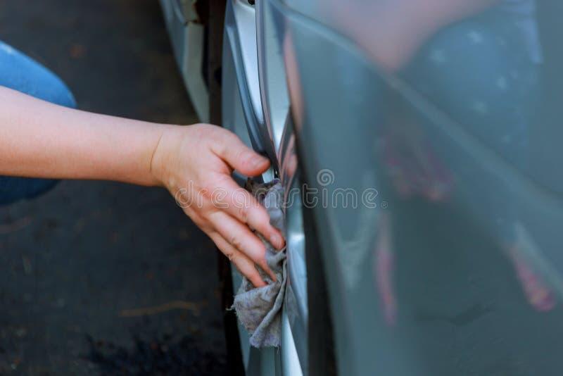 Mão com a roda de carro da limpeza de pano do microfiber foto de stock royalty free