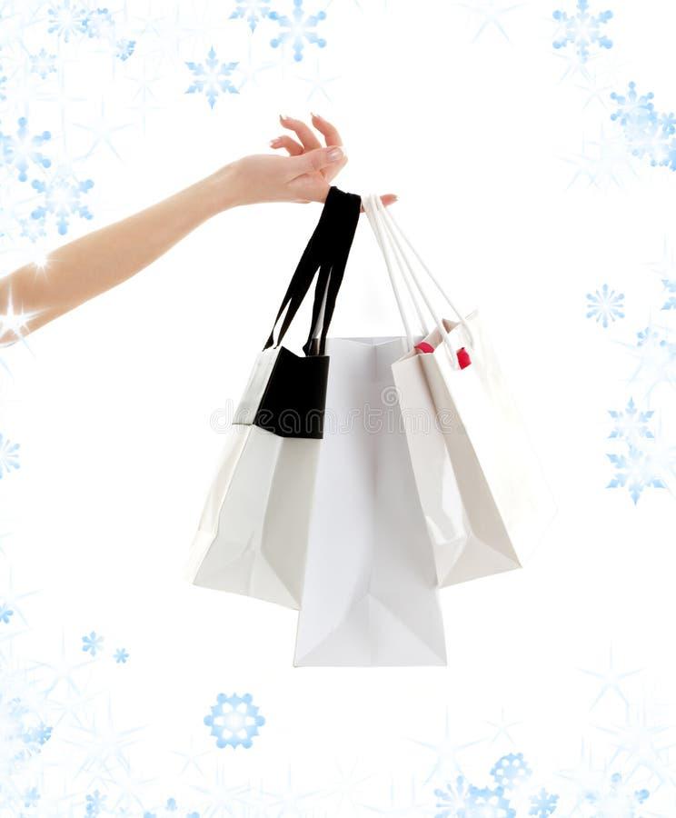 Mão com sacos e flocos de neve de compra foto de stock royalty free