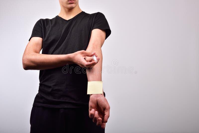 Mão com a seringa da heroína com post-it vazio fotografia de stock