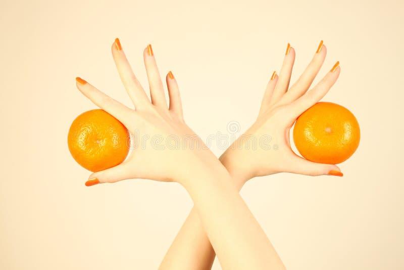Mão com tangerine alaranjado. foto de stock royalty free