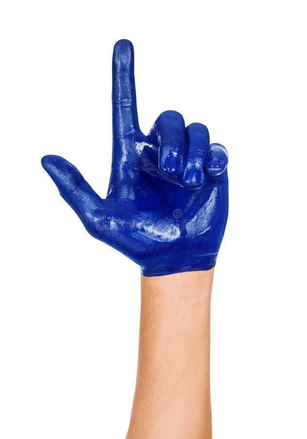 Mão com um indicador aumentado, pintado na pintura azul isolado fotografia de stock