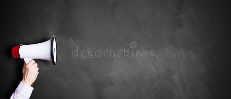 Mão com um megafone na frente de um quadro-negro imagens de stock