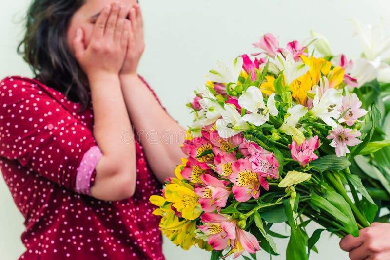 a mão com um ramalhete luxúria das flores estende flores a uma mulher que cubra sua cara com suas mãos fotografia de stock royalty free