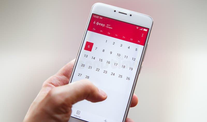 A mão com um smartphone com um calendário, um mês planeia fotos de stock