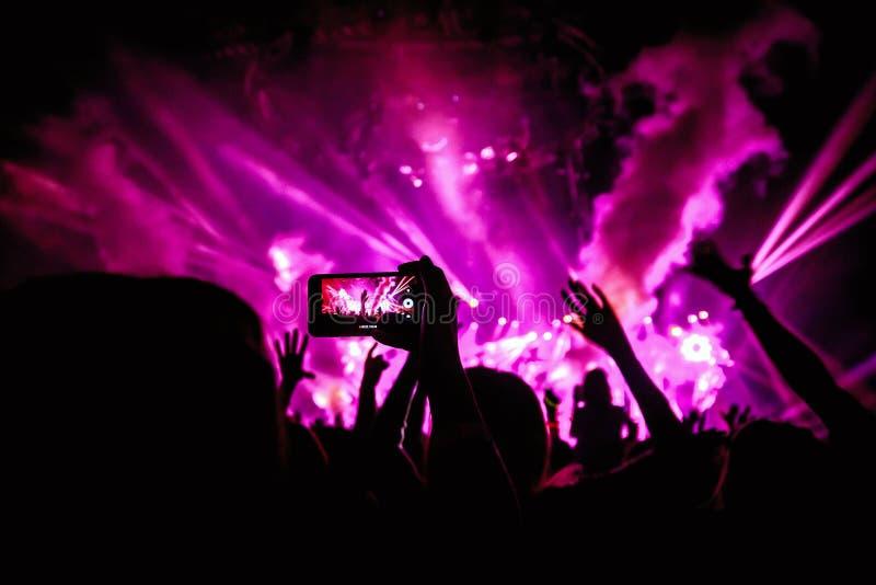 A mão com um smartphone grava o festival de música ao vivo, tomando a foto da fase do concerto fotografia de stock royalty free