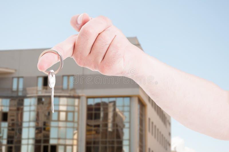Mão com uma chave da casa no close up fotografia de stock royalty free