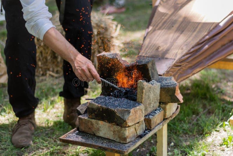 A mão com uma parte de ferro aquecida em um fogo de carvão e os foles fazem faíscas das ferramentas do ferreiro imagem de stock