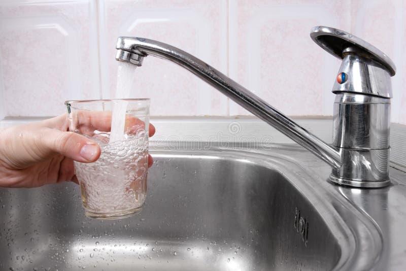 A mão com vidro da água derramou do torneira da cozinha fotos de stock