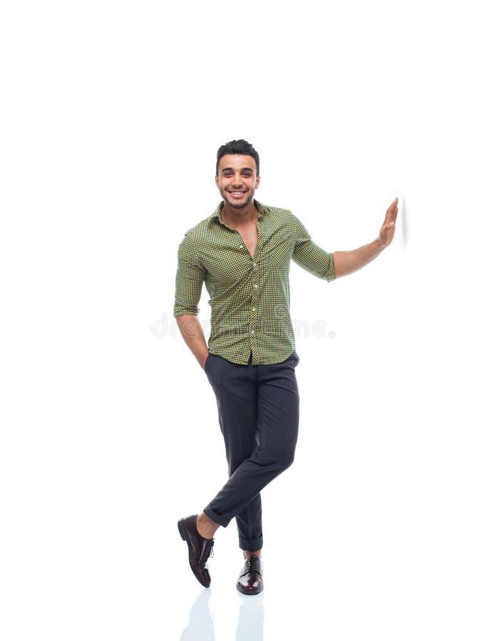 Mão considerável nova do indivíduo do sorriso feliz ocasional do homem de negócio no comprimento completo da parede fotografia de stock
