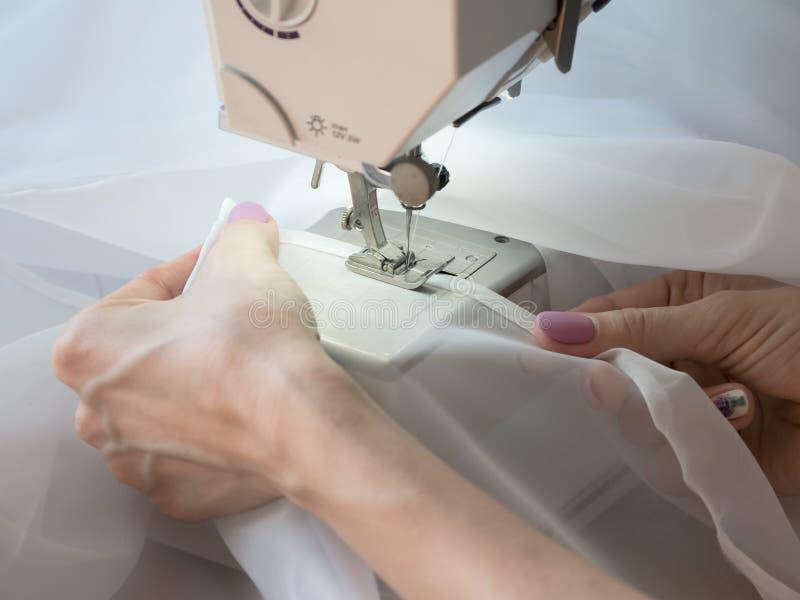 A mão costura um tule na máquina de costura fotos de stock royalty free