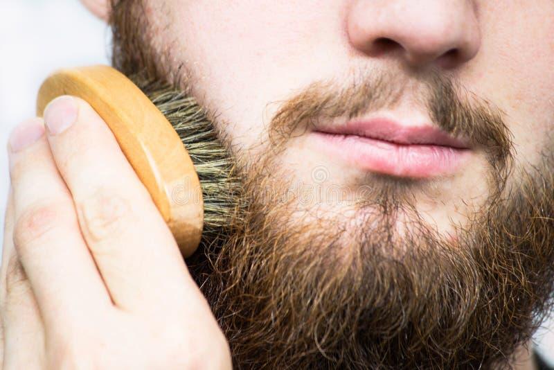 Mão da barba de escovadela do barbeiro Cliente do barbeiro, vista dianteira Pontas da preparação da barba para novatos fotos de stock royalty free