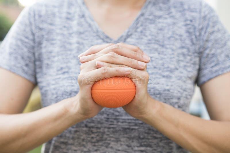 Mão da bola do esforço da terra arrendada da mulher imagens de stock